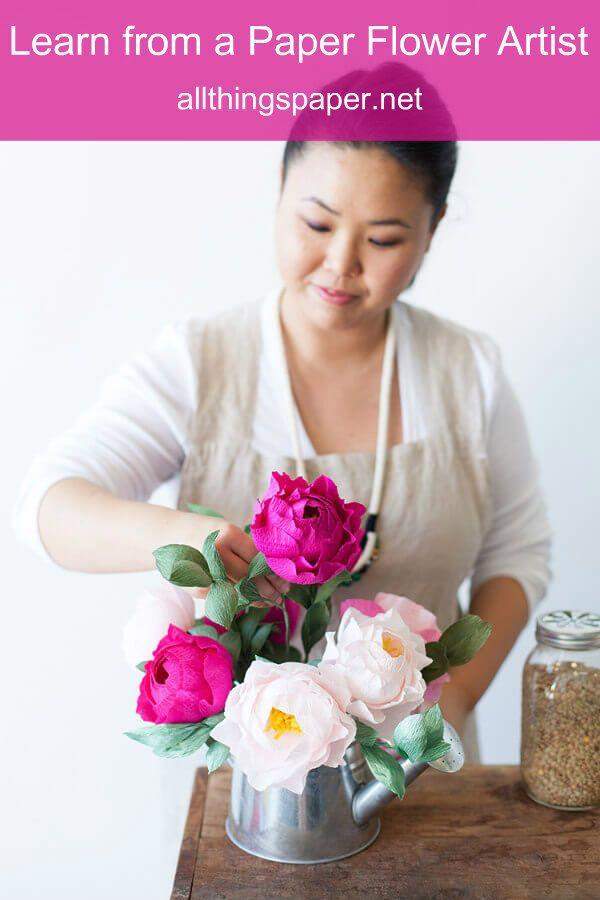 woman arranges crepe paper peonies in metal watering can