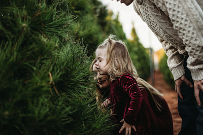 Baby making funny face smelling Christmas Trees at the Tree Farm for Photos in San Diego