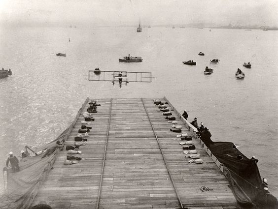 Photo of plane coming in to land on a wooden deck while sailors watch. 1911