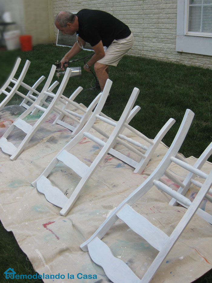 Spray painting chairs with pneumatic spray paint gun.