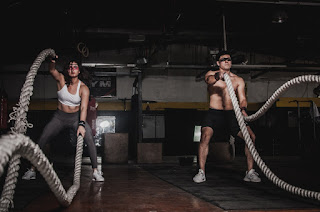 A man and a woman use ropes to exercise