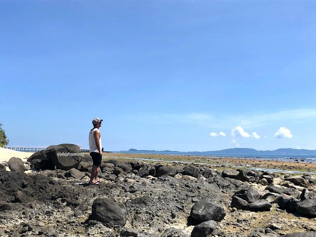 Karang dan bongkahan batu hitam di Pantai Paradise Likupang