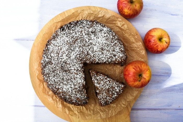 Vegan Red Apple & Treacle Fruit Cake on board drizzled with icing sugar, cut into slices