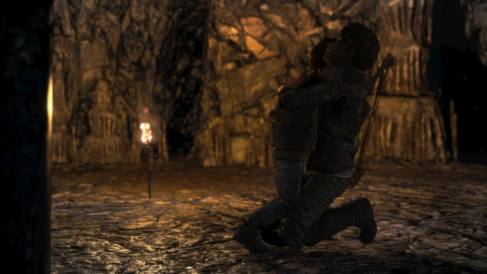 Clem és AJ szorosan átölelik egymást egy barlangban, egy földbe szúrt fáklya fényénél.