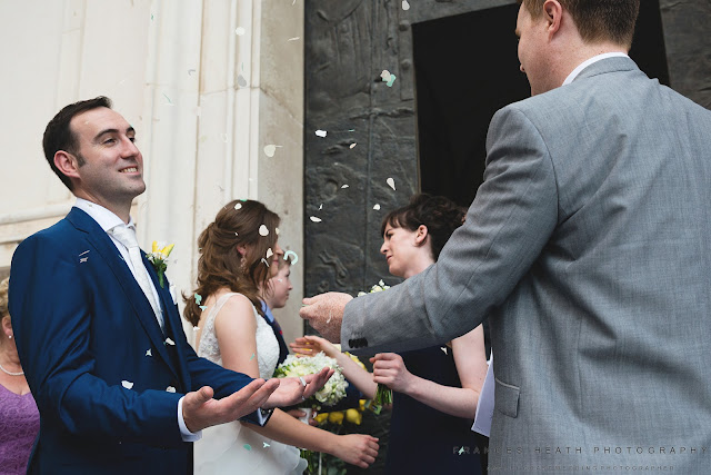 Guests throw confetti at bride and groom