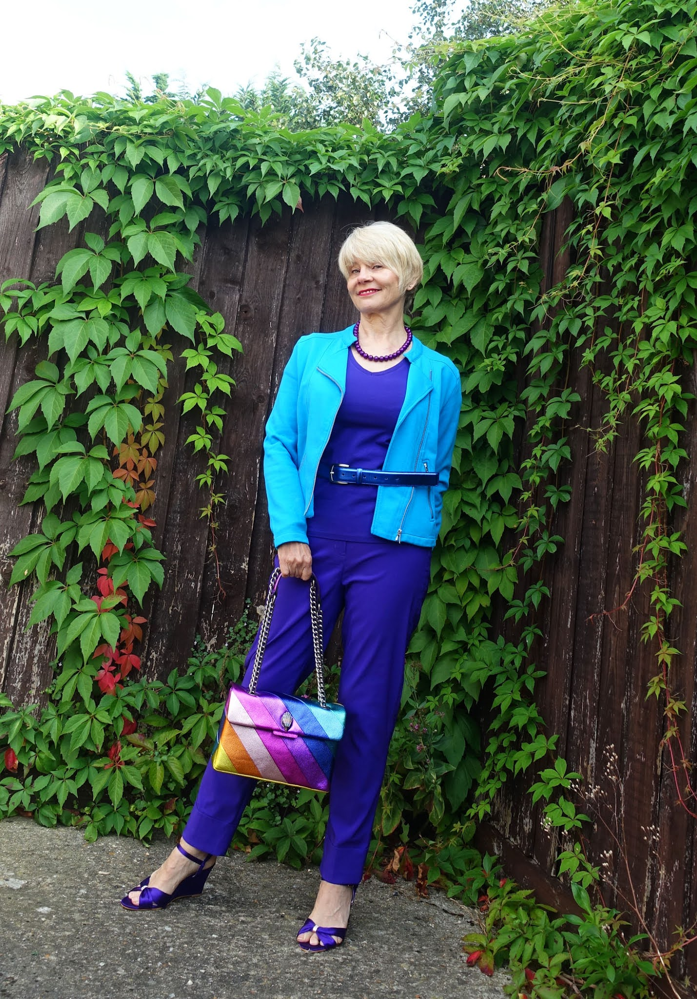 An outfit inspired by the Kurt Geiger Rainbow bag worn by Is This Mutton style blogger Gail Hanlon. Purple trousers, sandals and top with a vivid Blue Jewel jacket