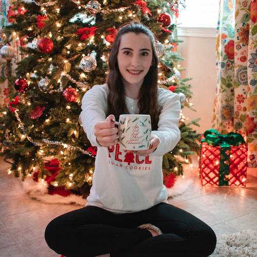 Madalyn sitting on floor in front of Christmas tree holding up the Names Of Jesus Ceramic Mug.