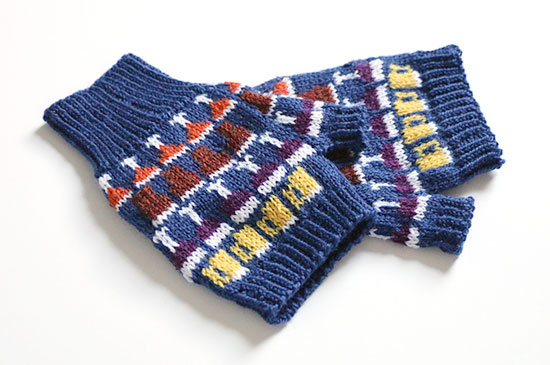Pair of hand knit colorwork Drinkers Mitts in blue with details in white, yellow, purple, brown and orange on a white background.