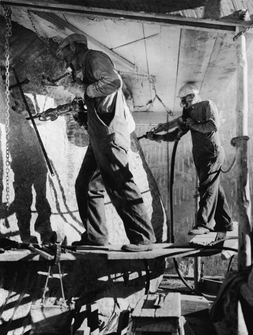 Builders with pneumatic jackhammers work to create an eye sculpture by President Theodore Roosevelt, part of the Mount Rushmore National Memorial, circa 1939.