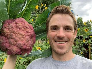 Farmer guy holding purple cauliflower