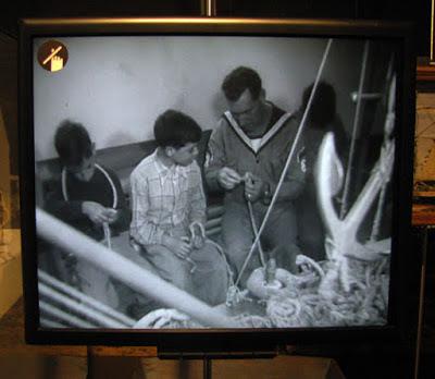 video de pescador a ensinar menino a fazer redes de pesca