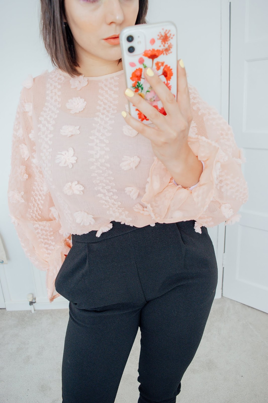 Person holding a phone wearing a pink blouse and black trousers.