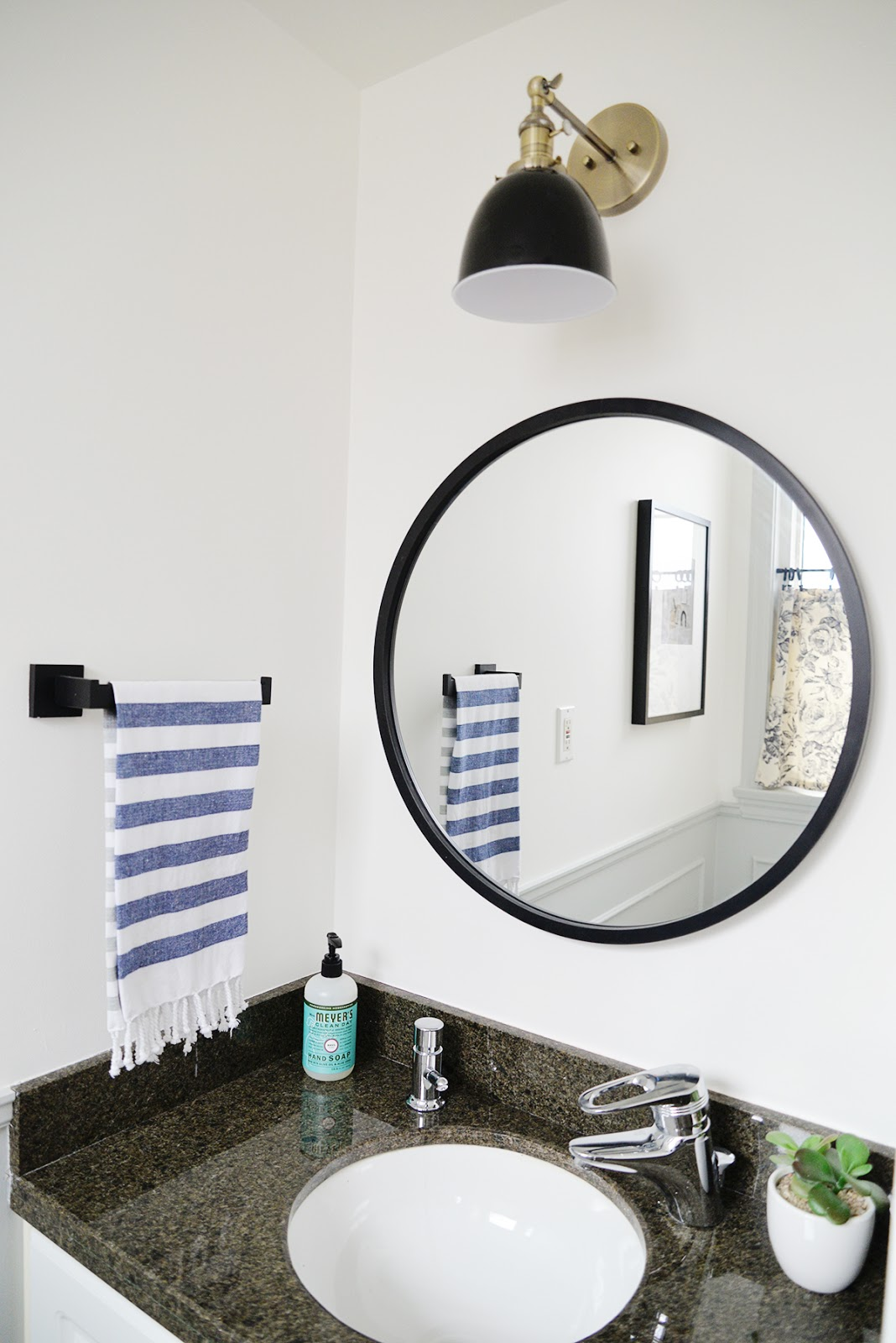 small powder room, round bathroom mirror, amazon sconce