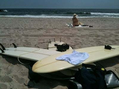 Pile of surfboards on Rockaway Beach with a girl sitting in the background