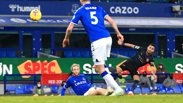 Manchester city winger Riyad Mahrez scores against Everton