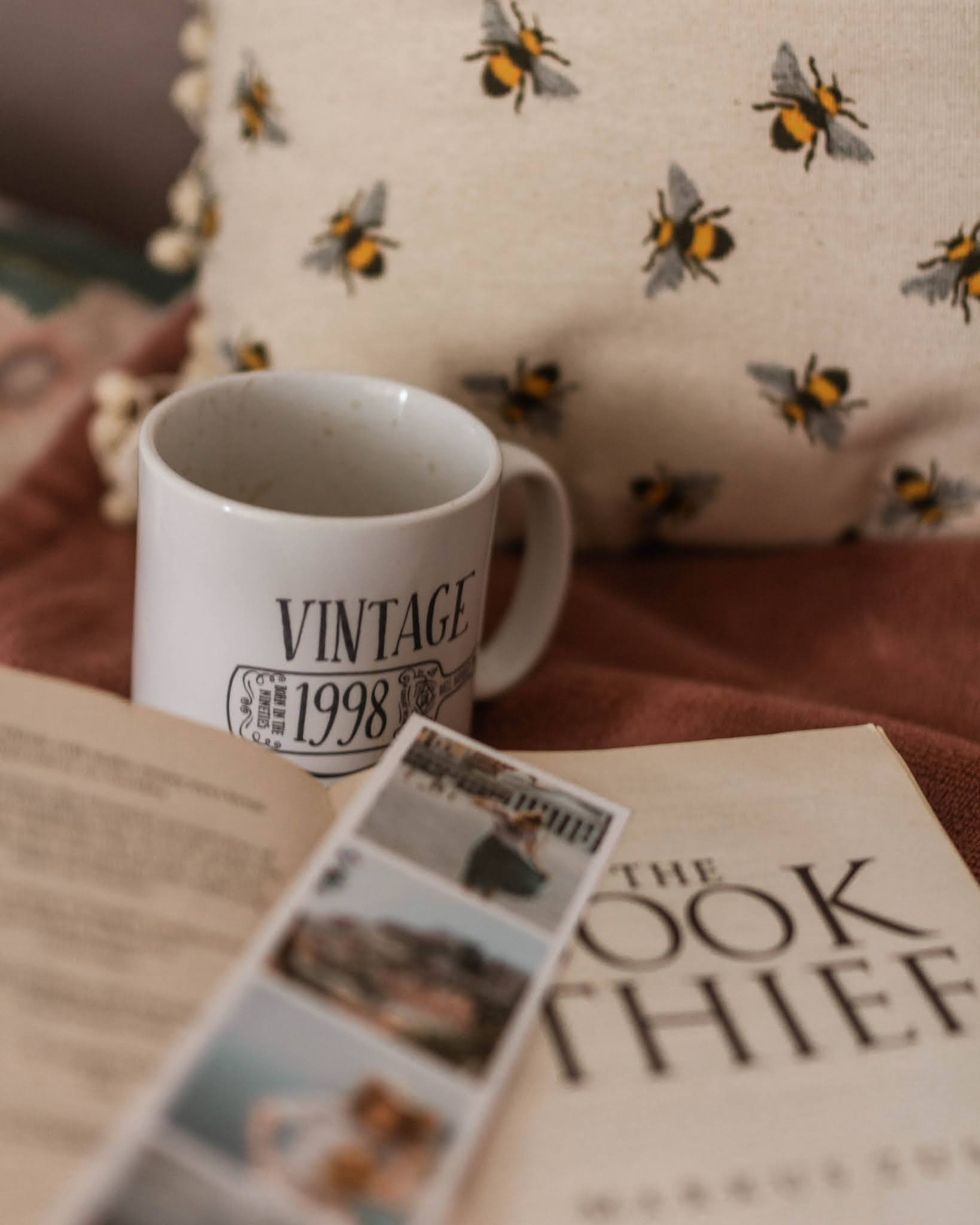 photo of open book the book thief by markus zusak sitting on bed with bookmark photostrip and white mug