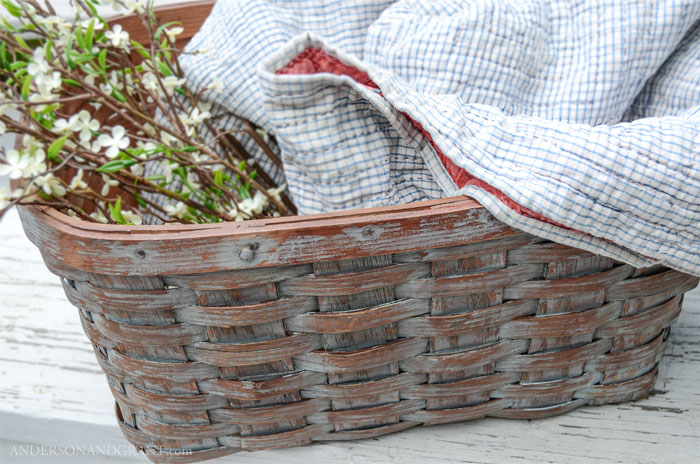 A broken picnic basket is repurposed as a useful place to store blankets or magazines.  See the DIY project at www.andersonandgrant.com