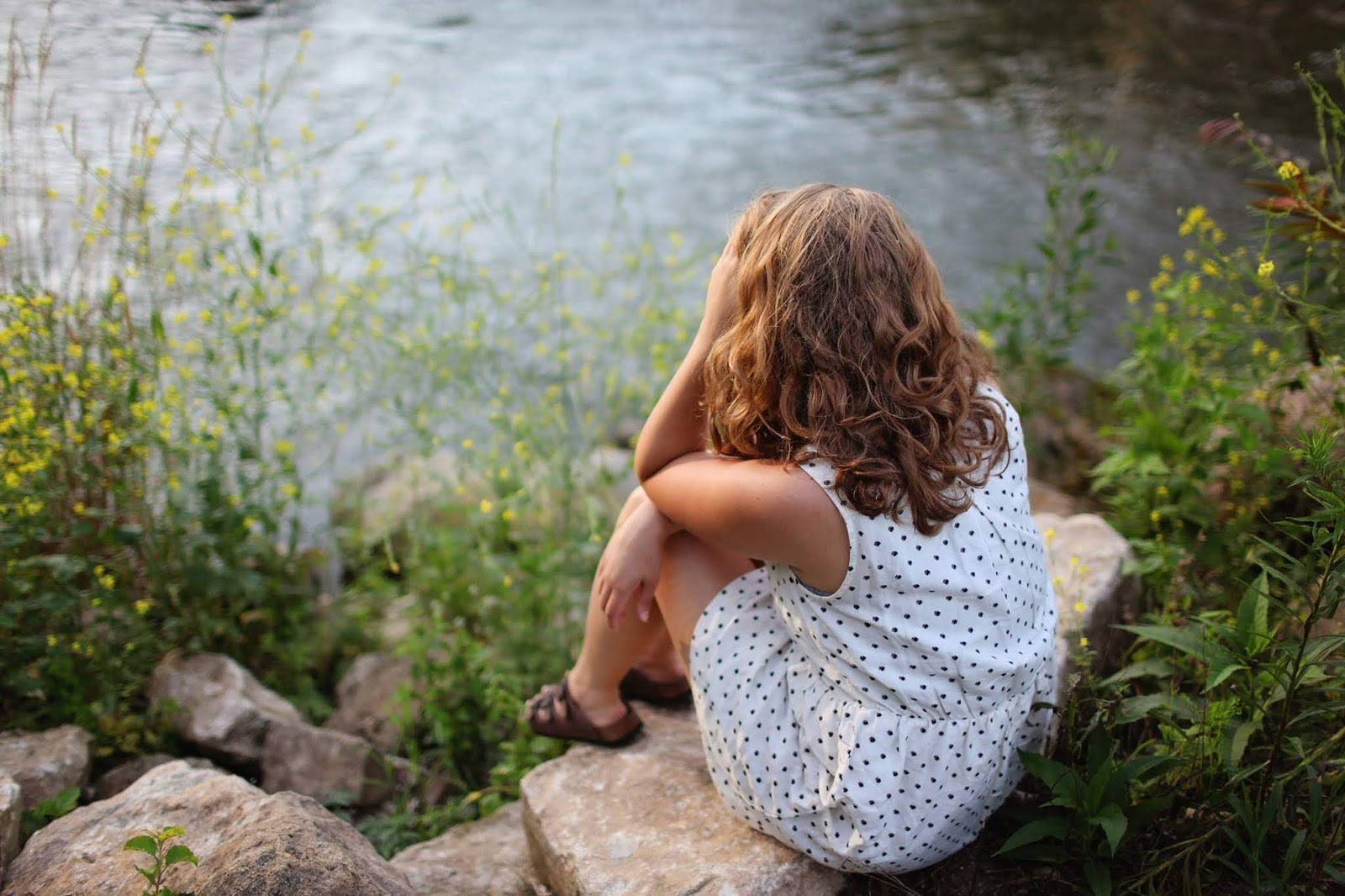 upset woman sitting by the river