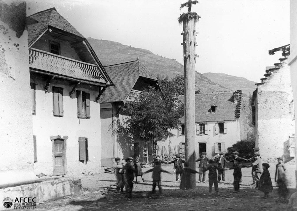 Plaça major de Lés amb l'haro de la festa de Sant Joan i nens ballant al voltant (Juli Soler 1890-1914, Arxiu Fotogràfic del CEC).