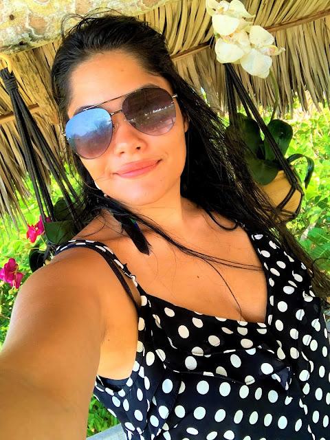 selfie de mulher com oculos escuro, cabelo preto e blusa de bolinha branca