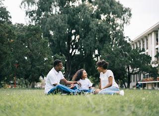 Gambar Keluarga Duduk Bersama di Atas Rumput