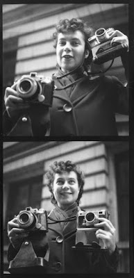 black and white photograph of young Ida Wyman with 2 of her cameras