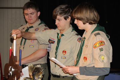 Liam, Joe and Everett (left to right) light candles signifying the principles behind the colors of the American flag, which are also found in Eagle Scout badge.