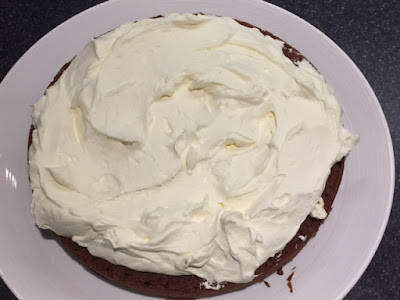Bottom layer of chocolate cake with whipped cream spread over the top