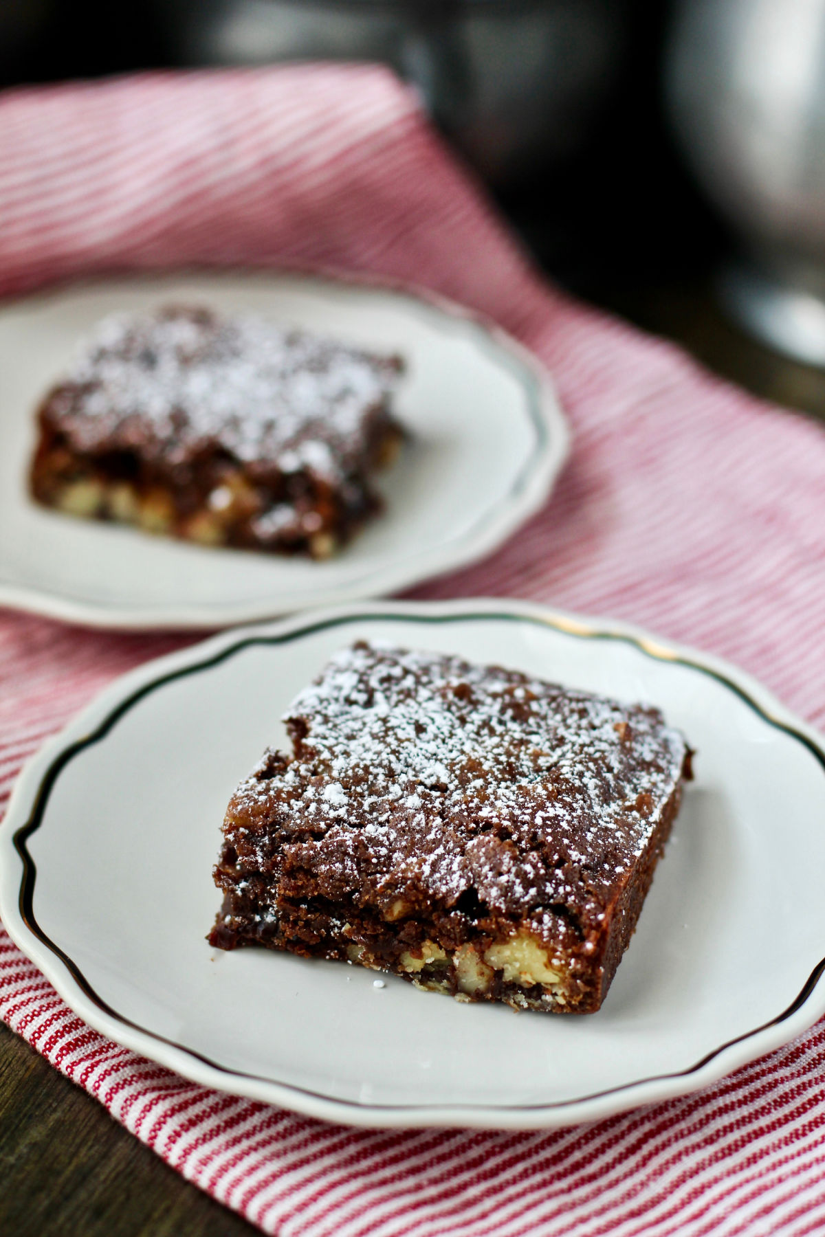 Fudge Cake with Cherries and Pecans slices on plates