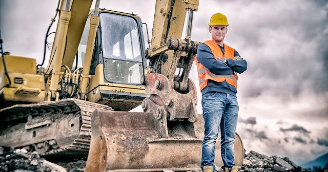 man in construction gear stands in front of heavy equipment