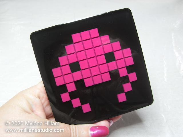 Hand holding the finished bright pink and black jellyfish space invader resin coaster