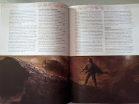 A two-page spread, with text filling the top half of both pages, and a painting of a men riding sandworms spreading across the bottom half of both pages.