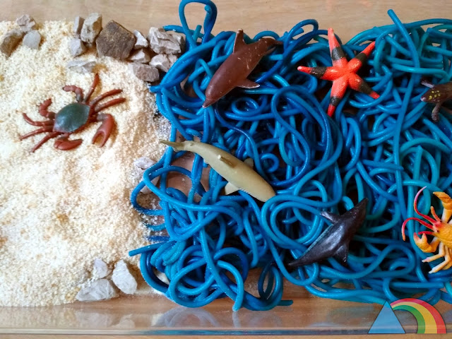 Mini mundo marino hecho con pan rallado y espaguettis teñidos de azul