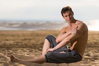 homem sem camisa passando protetor solar na pele em frente a praia