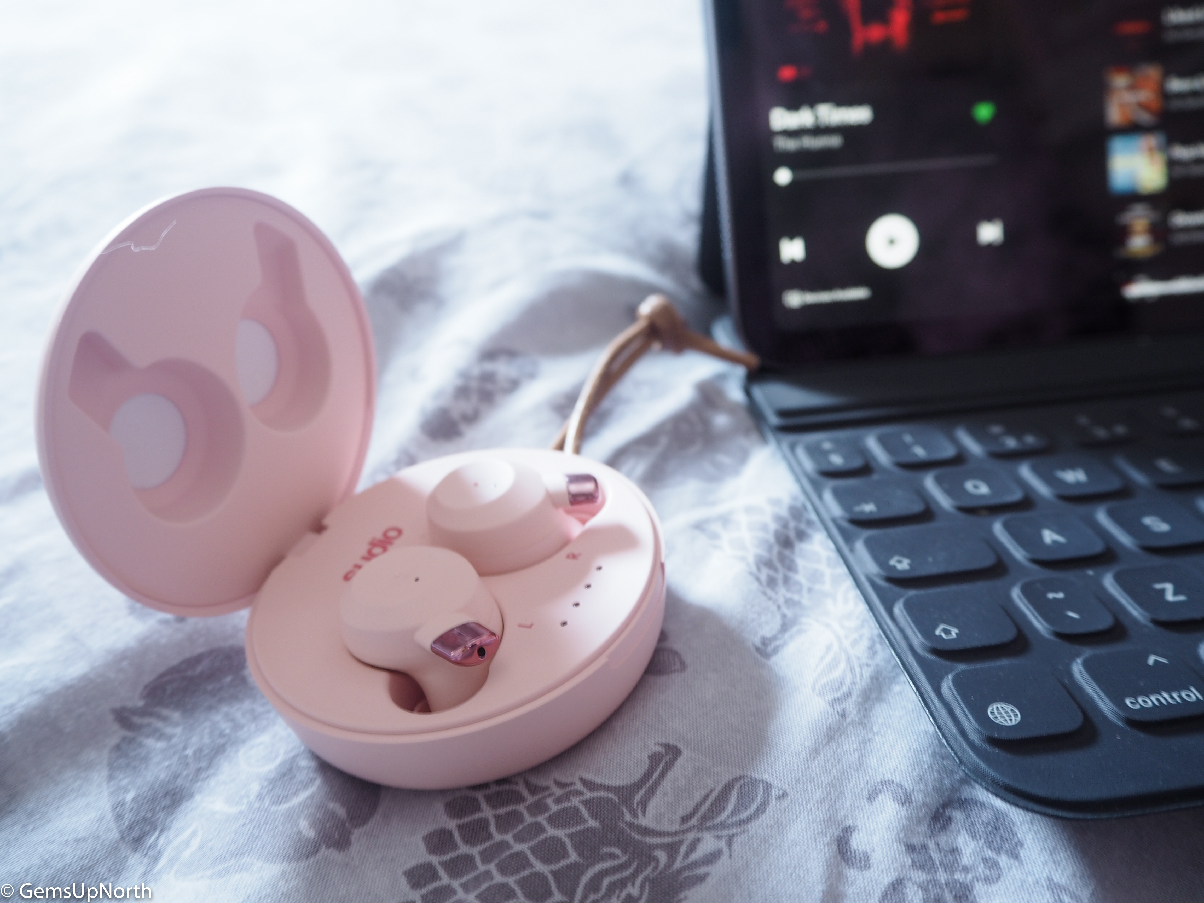 Pink FEM Sudio Ear buds, open in charging case next to an iPad with Spotify playing