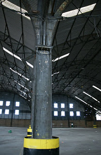 Photograph of the interior with steel pillars and struts and a corrugated iron roof. The interior is otherwise empty; the front gable wall and windows are visible in the distance.
