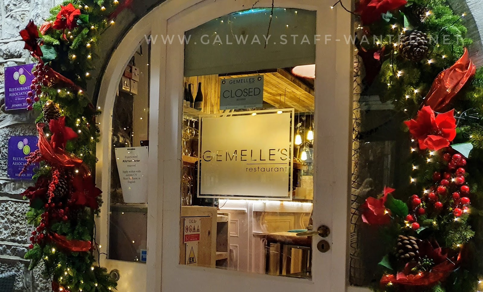 restaurant doorway with holly-berry wreath christmas decoration encircling it