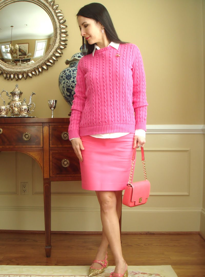 Wearing a bright pink sweater with a spider brooch. A light pink button down underneath and a bright pink pencil skirt. Carrying a pink purse.