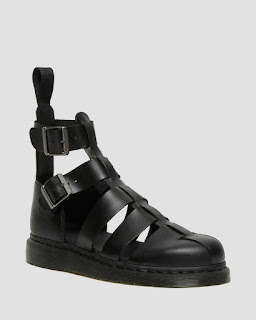 A photo of some black sandals with leather straps at the top that fit the ankle with a closed toe feature at the bottom to make them look more like shoes on a bright background
