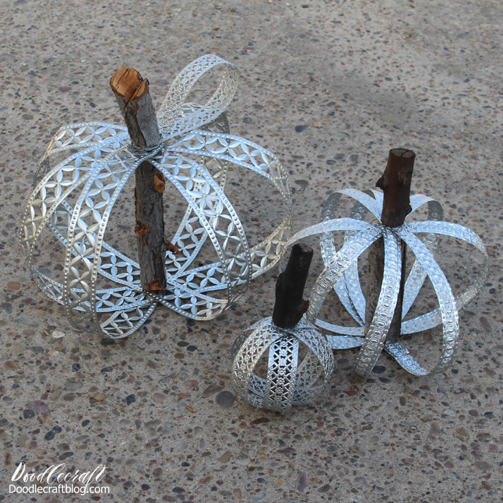 Rustic pumpkins made with metal ribbon and tree branches.