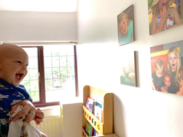 Baby Boy smiling at photographs on nursery wall