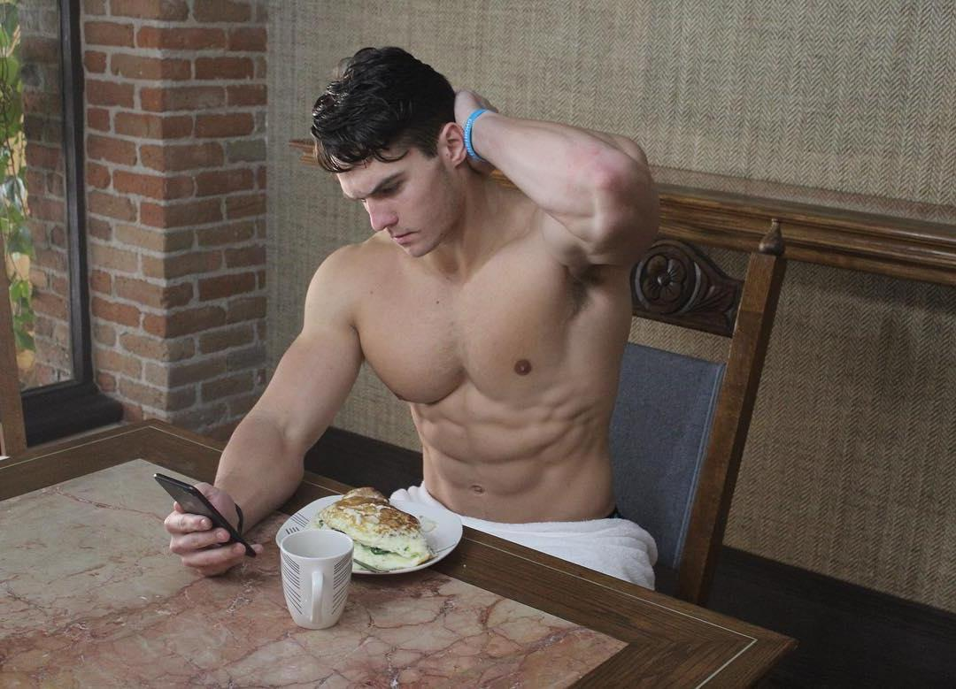 good-looking-fit-muscle-pecs-male-athlete-sixpack-abs-texting-phone-breakfast