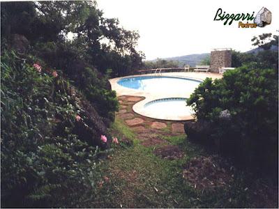 Construção da piscina em alvenaria com os muros de pedra, os caminhos de pedra com pedras ornamentais.