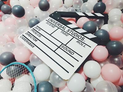 Claqueta de cine rodeada de globos de colores