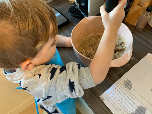 Boy mixing muffins ingredients in a bowl