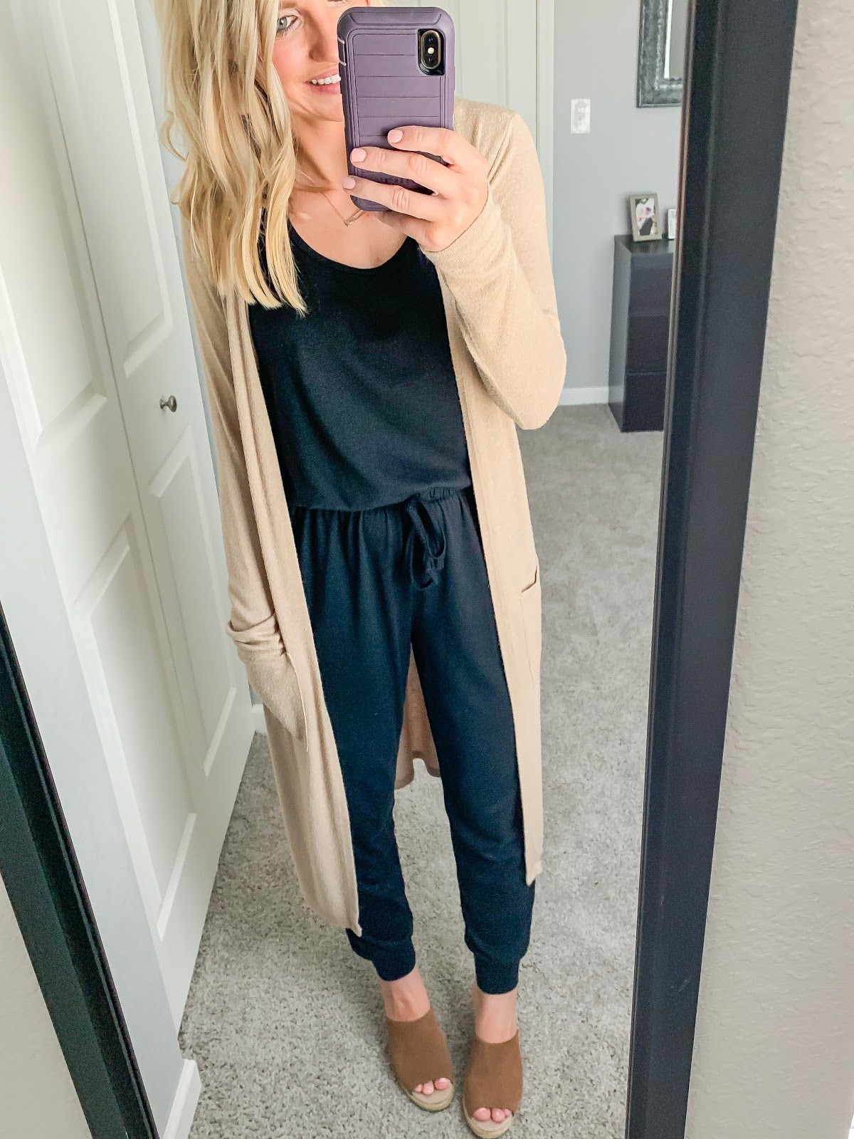 Black jumpsuit styled with a tan duster cardigan