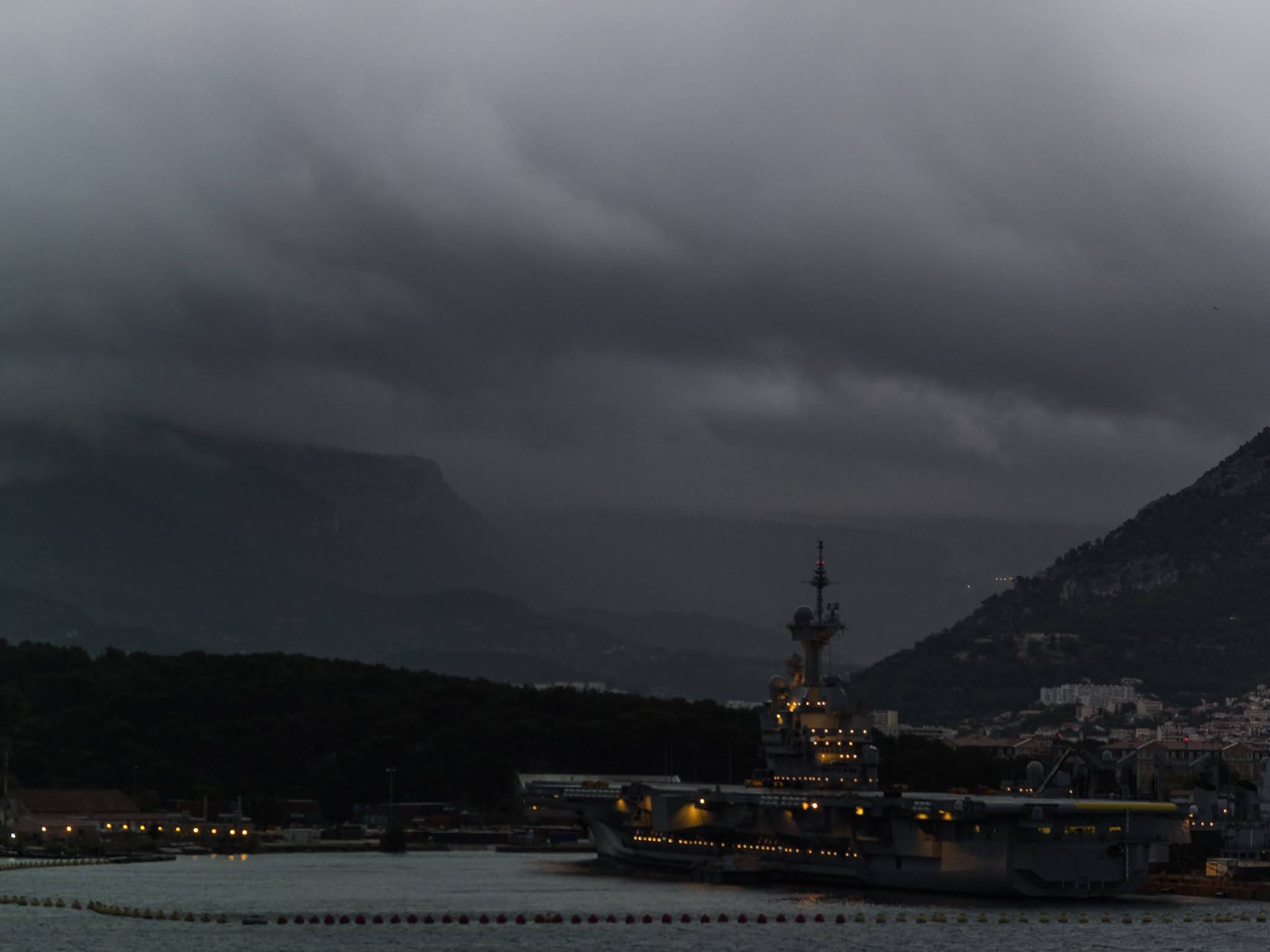 Ship in Toulon harbour with clouds coming down the mountains.