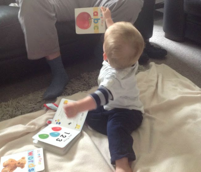 Baby holding up abc book to adult