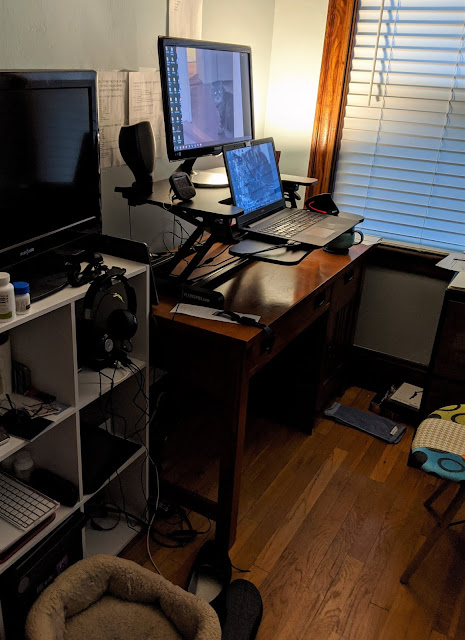 The same desk set up but there is a standing desk unit on the desk that holds both the laptop and the monitor.