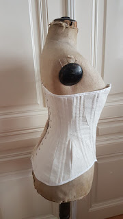 side view of the edwardian corset on an edwardian dress form